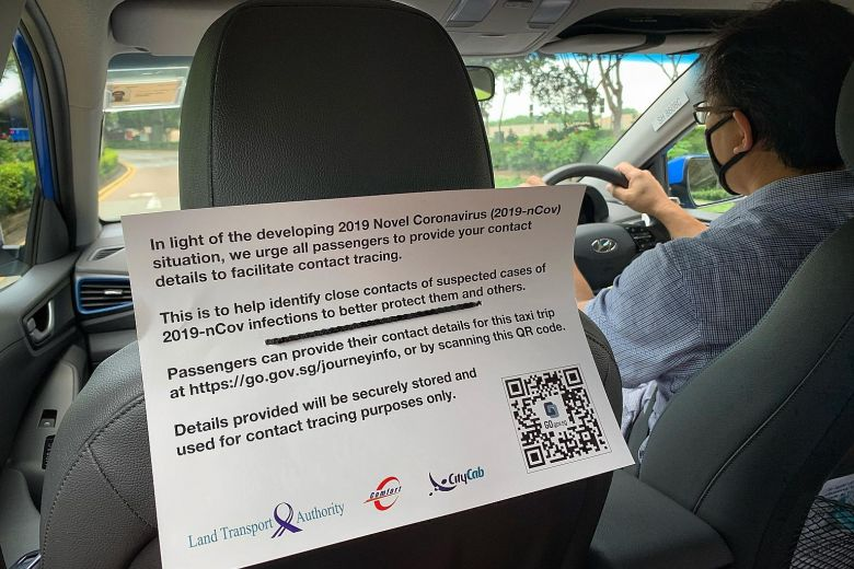A notice in a ComfortDelGro taxi asking passengers to provide their contact details for the trip