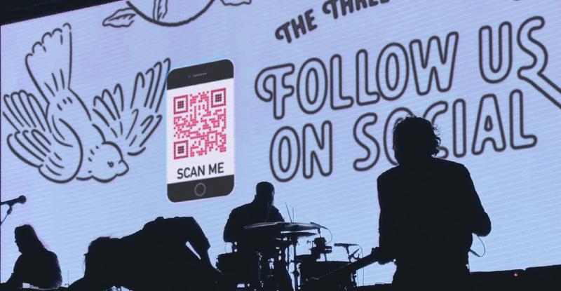 Digital screen at a concert featuring a QR Code.