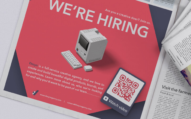 QR Code in a print newspaper ad prompting readers to scan to watch an informational company video