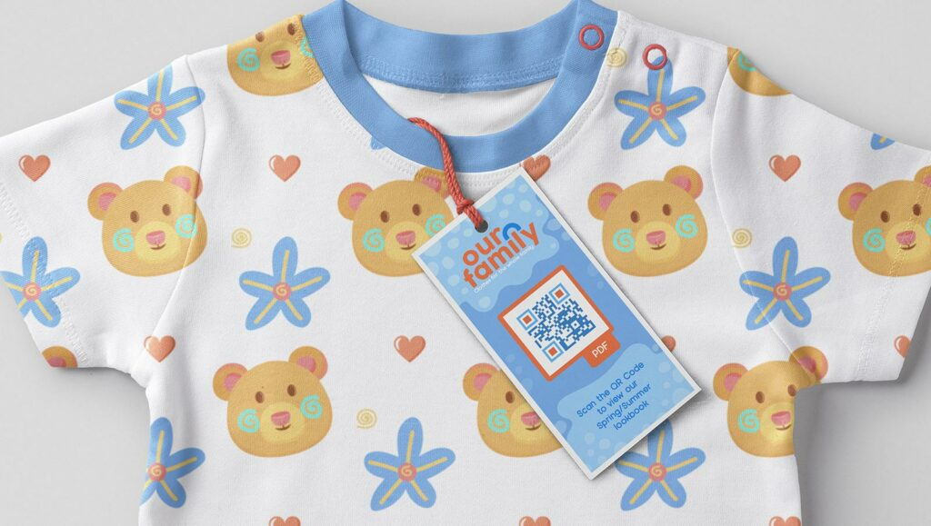 PDF QR Code on a baby shirt clothing tag prompting buyers to scan and view the company's spring/summer look book
