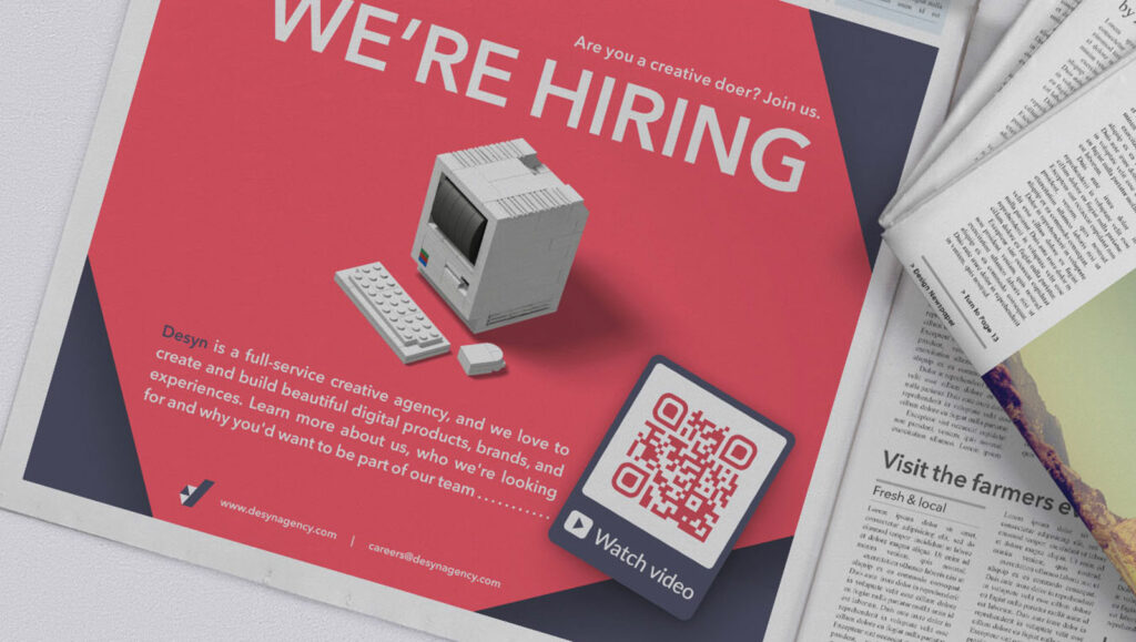 Video QR Code in a print newspaper ad prompting readers to scan and watch a video about the company