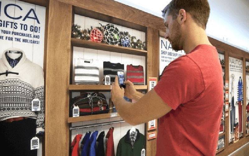 A man scanning a QR Code on a shoppable wall
