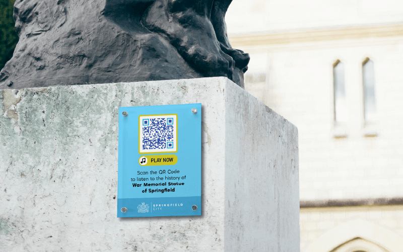 An MP3 QR Code on a historic statue prompting people to scan and listen to the history of the statue.