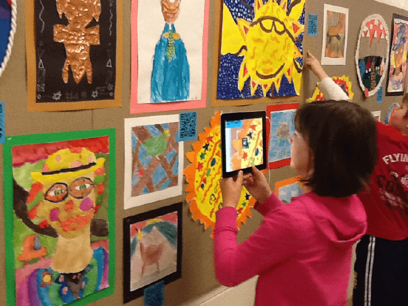 An interactive QR Code art wall in a classroom displaying students' artwork