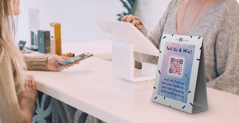 Feedback QR Code on a boutique's table tent prompting shoppers to scan and leave feedback for a chance to win a shopping spree