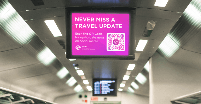 QR Code on digital signage in public transportation prompting passengers to scan for up-to-date travel news on social media