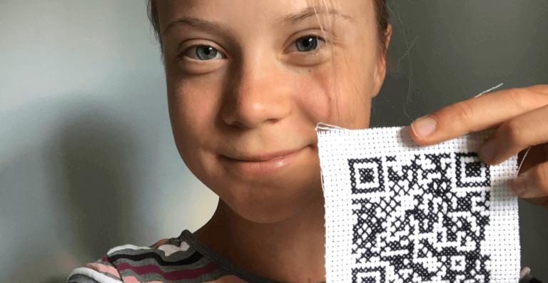 Climate activist Greta Thunberg holding up an environmentally friendly QR Code